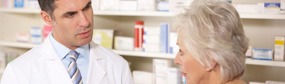 Ein Apotheker mit Krawatte berät eine ältere Patientin in einer Apotheke.