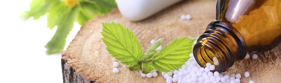 Globuli, ein umgekipptes, geöffnetes Arzneifläschchen und grüne Blätter liegen auf einem Baumstumpf.