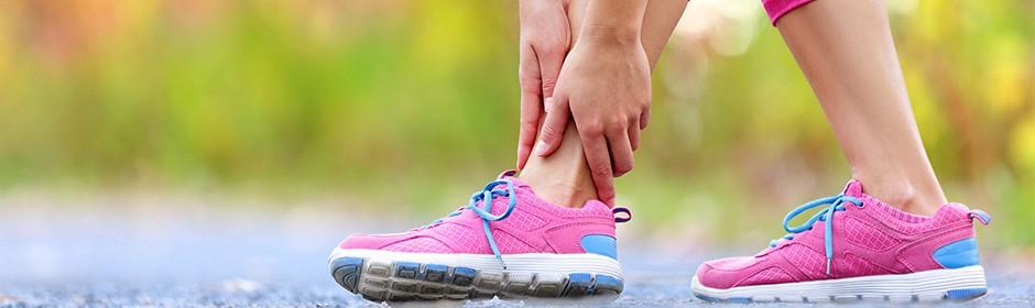 Eine Läuferin fasst sich an den schmerzenden Knöchel.