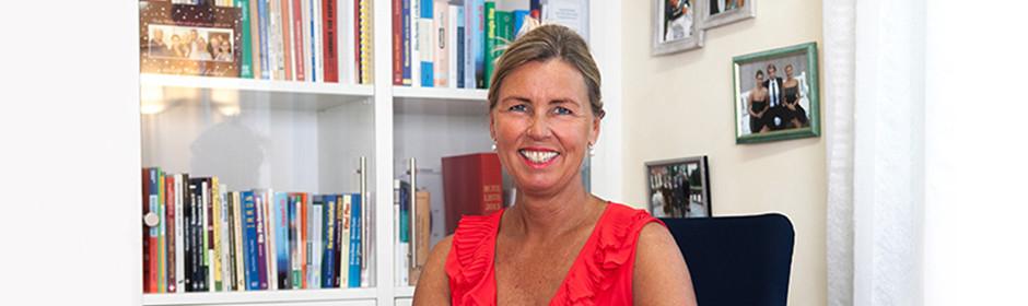 Ärztin Dr. Michaela Ludwig steht zur Homöopathie. Sie sitzt auf einem Stuhl vor einem Bücherregal und einer Wand mit Fotos.