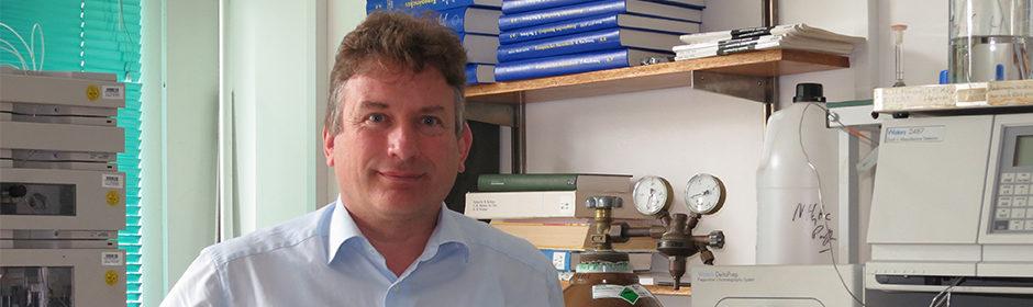 Prof. Dr. Michael Keusgen steht vor einem Regal in seinem Labor.