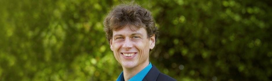 Porträtfoto von Dr. Jens Behnkes vor einem grünen Hintergrund
