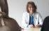 Dr. Maria Möller trägt einen Arztkittel und ein Stetoskop und sitzt an einem Tisch zwei Frauen gegenüber. Die Frauen sind von hinten zu sehen und tragen beide ein Kopftuch.