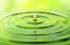 Wassertropfen fallen auf eine Wasseroberfläche und kreisförmige Wellen entstehen auf einem grünen Hintergrund.